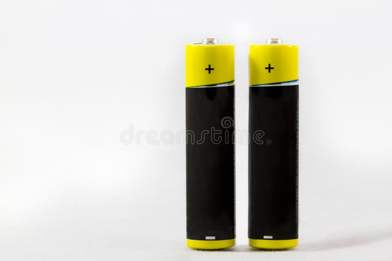 Deux accumulateurs alcalins jaune-noirs debout de D.C.A. d'isolement sur le whi photo libre de droits