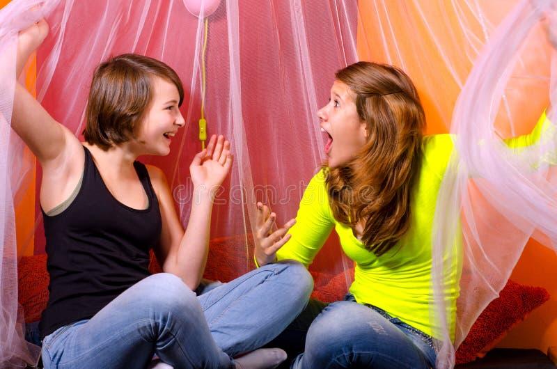 Deux adolescentes ayant l'amusement sur le lit photos stock