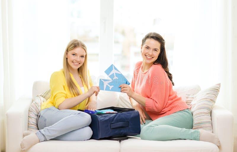 Deux adolescentes de sourire avec des billets d'avion photographie stock libre de droits