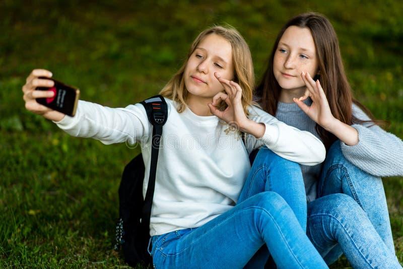 Deux adolescentes En été en nature de parc Reposez-vous sur l'herbe derrière des sacs à dos Dans des ses mains tient le smartphon photos libres de droits