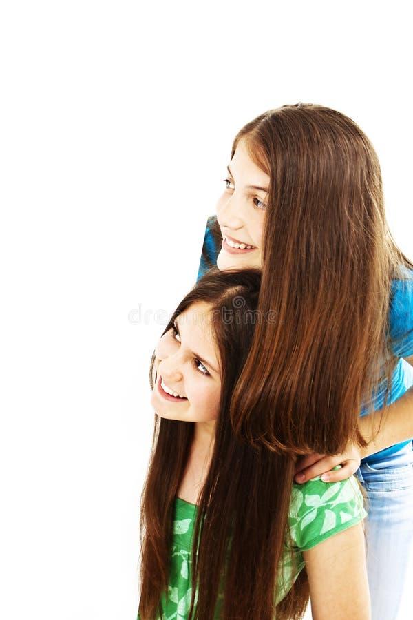 Deux adolescentes heureuses regardant le panneau-réclame blanc photo stock
