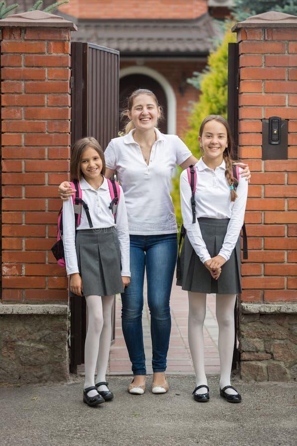 Deux adolescentes posant avec la mère devant la grande maison avant d'aller à l'école photo stock