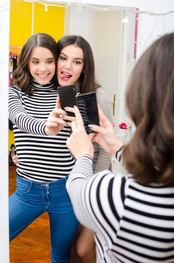 Deux adolescentes prenant des photos de selfie devant le miroir image libre de droits