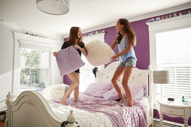 Deux adolescentes se tenant sur un lit ayant un combat d'oreiller images libres de droits