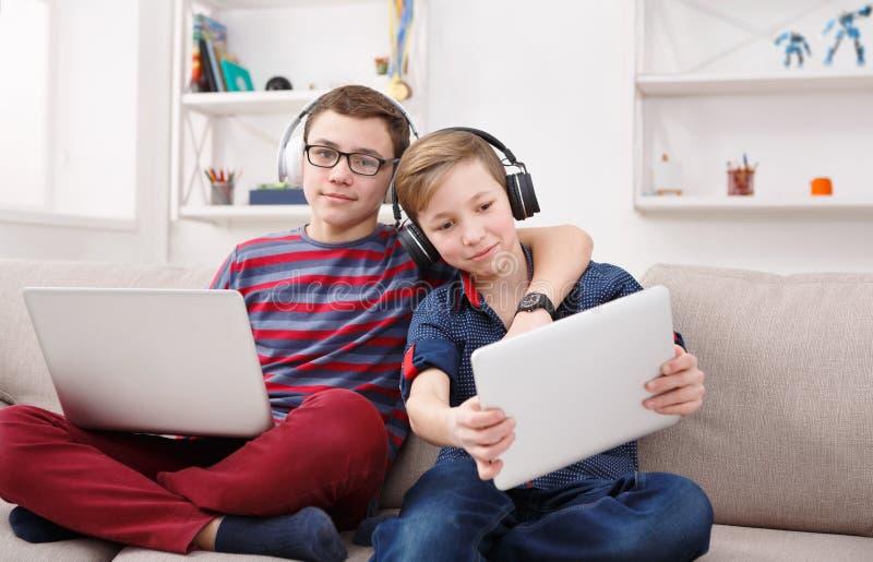 Deux adolescents à l'aide du comprimé sur le divan à la maison photo libre de droits