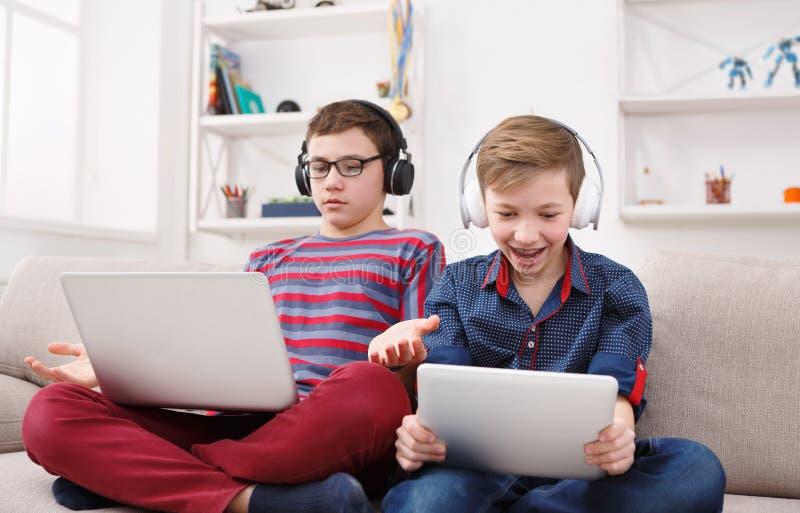 Deux adolescents à l'aide du comprimé sur le divan à la maison photos stock