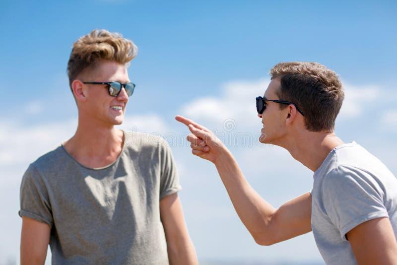 Deux adolescents parlant sur un fond de ciel bleu Jeunes jolis types dans des lunettes de soleil Deux types de argumentation Conc photo stock