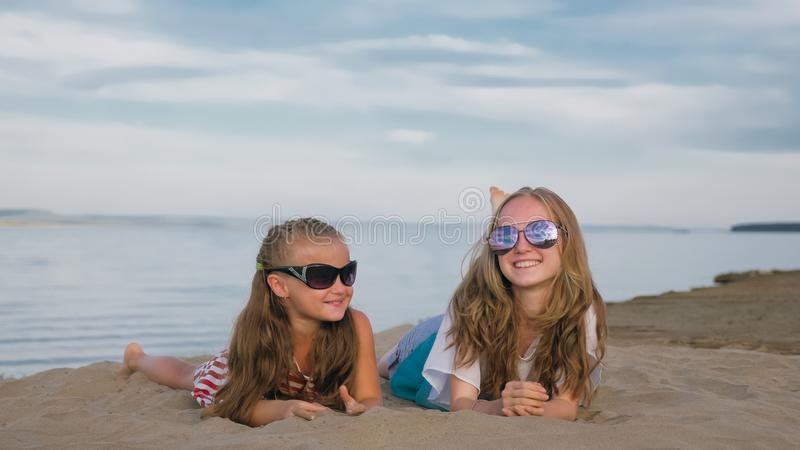 Deux adolescents s'asseyent sur la plage photographie stock libre de droits