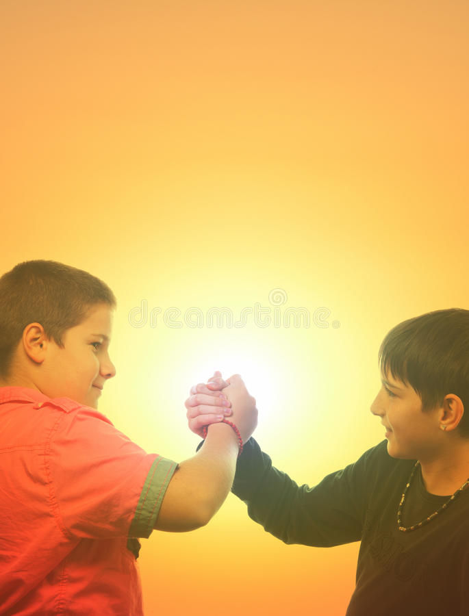 Deux adolescents se serrant la main en été images libres de droits