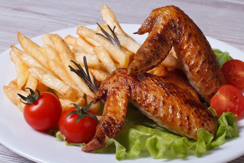 Deux ailes de poulet frit, pommes frites, tomates et laitues photographie stock libre de droits