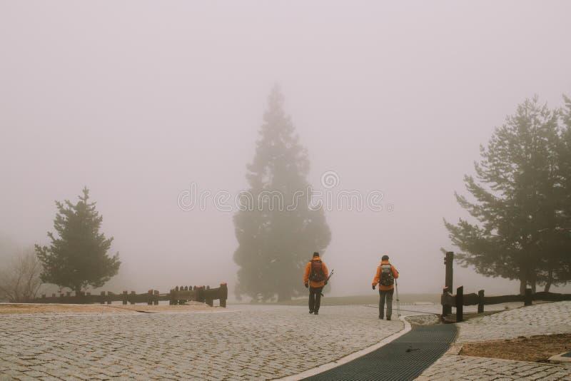 Deux alpinistes marchent dans le brouillard épais photo libre de droits