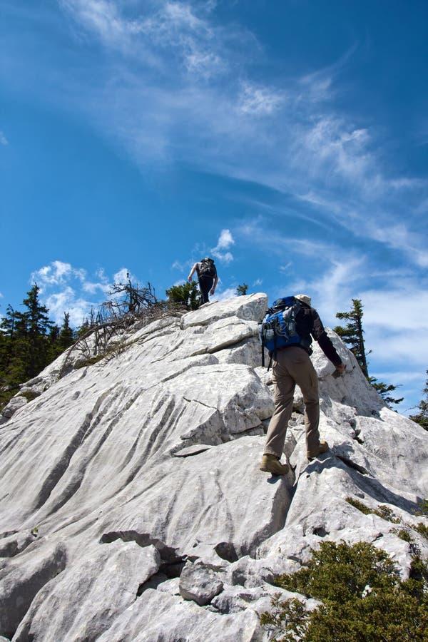 Deux alpinistes trimardant jusqu'au dessus de la montagne images libres de droits