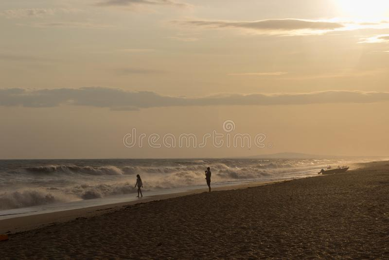 Deux amants marchant sur la plage d'or par des lumières de coucher du soleil près du vieux bateau images stock