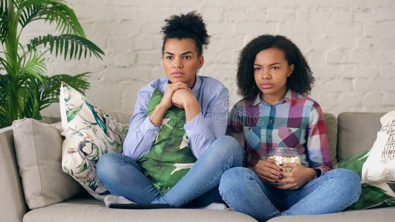 Deux amie bouclés de métis s'asseyant sur le film de thriller de divan et de montre et mangent du maïs éclaté à la maison image stock