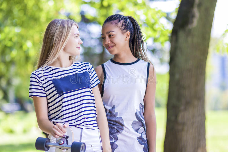 Deux amies adolescentes ainsi que Longboard dehors en parc image libre de droits