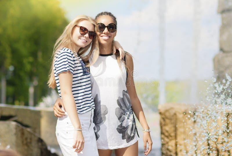 Deux amies adolescentes ensemble Pose contre la fontaine en parc dehors photographie stock libre de droits