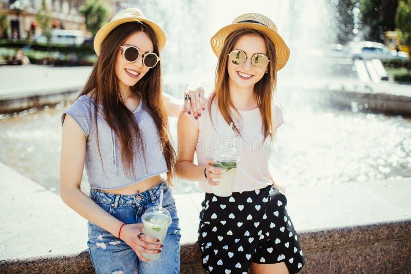 Deux amies ayant l'amusement extérieur en été à la marche dans la rue près du mojito fountaing de boissons Femmes avec des verres photo libre de droits