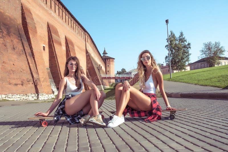 Deux amies de filles, soeurs en été dans la ville s'asseyent sur les panneaux, longboard de patin Figure bronz?e longs par cheveu photographie stock libre de droits