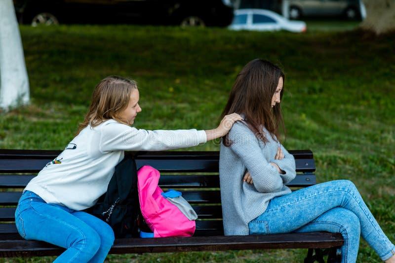 Deux amies en été sur le banc Offensé Les amis se sont disputés Nigativa parmi des filles Le problème est dedans photos libres de droits