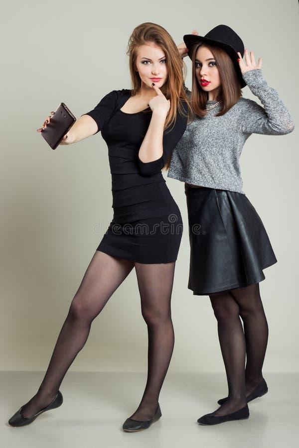 Deux amies heureuses gaies de fille ont photographié au téléphone, téléphone d'individu photographie stock libre de droits