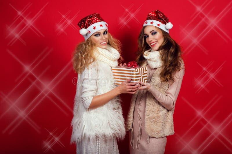 Deux amies magnifiques avec briller sourit les chapeaux de port de Santa et chauffe les écharpes de laine donnant la boîte actuel image libre de droits