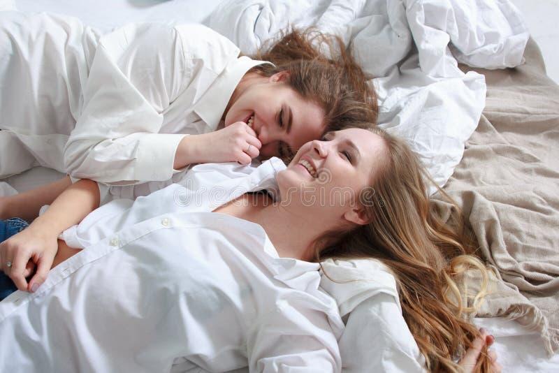 Deux amies riant et étreignant dans le lit pendant le matin photographie stock