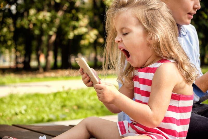 Deux amis adolescents heureux employant au téléphone portable tout en détendant dans le parc Problèmes de la jeunesse moderne, ré photo libre de droits