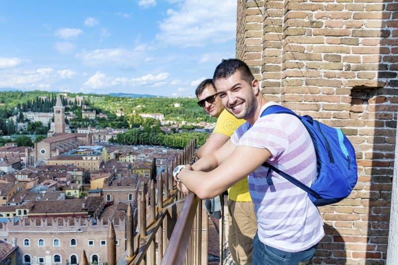 Deux amis d'hommes regardant au-dessus du balcon dans la ville de Vérone, Italie images stock