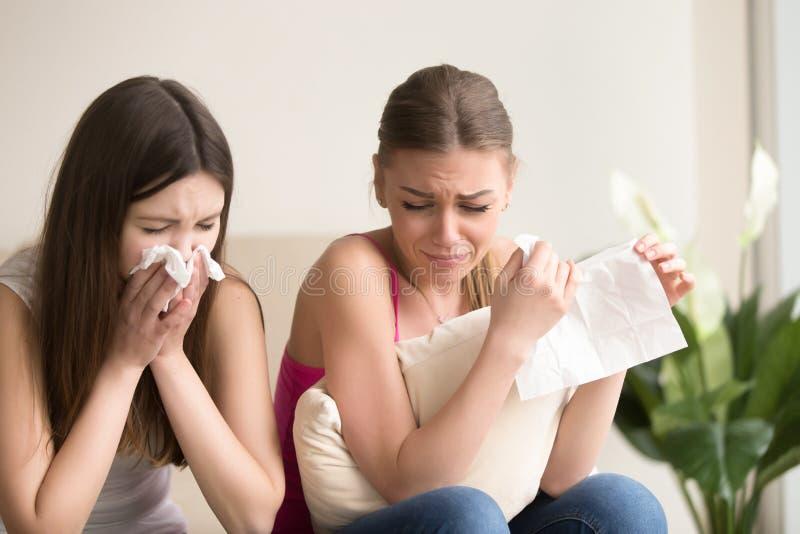 Deux amis de jeunes femmes pleurant ensemble à la maison images libres de droits