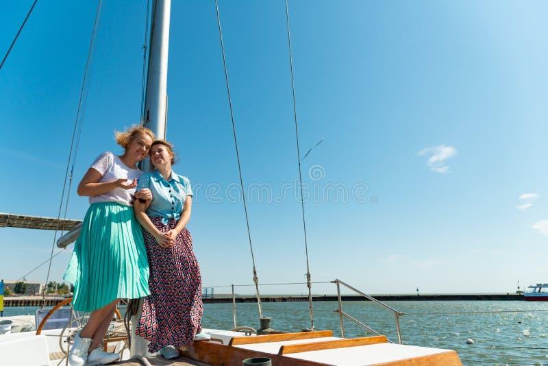 Deux amis embrassent sur un yacht près du mât et rêvent de l'avenir images libres de droits