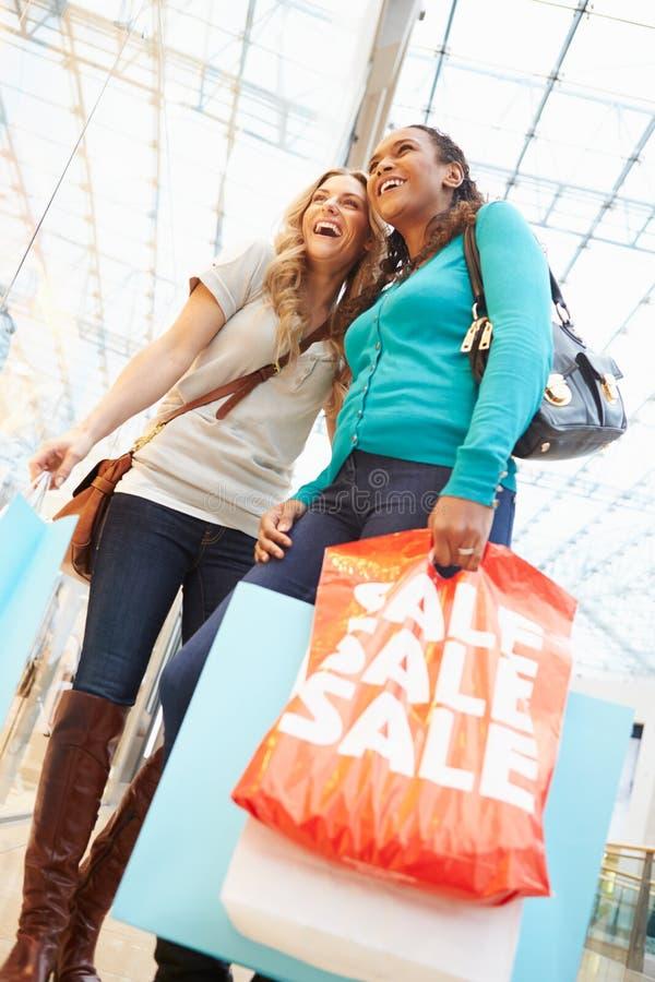 Deux amis féminins avec des sacs dans le centre commercial image libre de droits