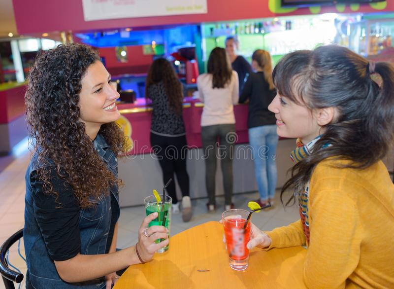 Deux amis féminins buvant des doux à la barre photos stock