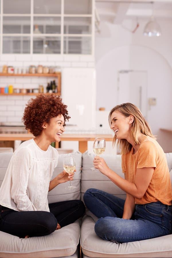 Deux amis féminins détendant sur Sofa At Home With Glass de vin parlant ensemble photos libres de droits