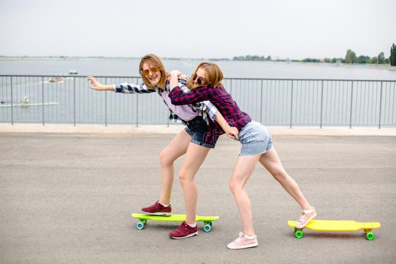 Deux amis féminins de sourire apprenant le longboard de monte avec s'aider Concept d'amitié photographie stock libre de droits