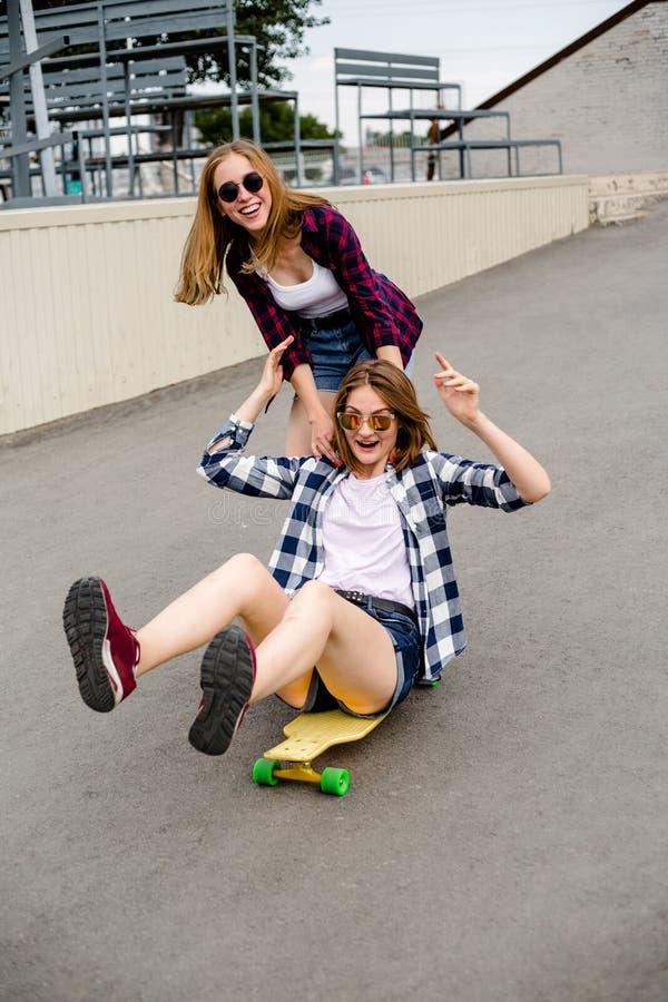 Deux amis féminins de sourire ayant l'amusement montant le longboard jaune sur la rue Concept d'amitié images stock