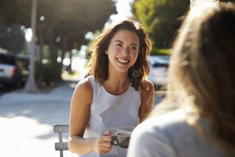 Deux amis féminins parlant au-dessus du café en dehors d'un café photos stock