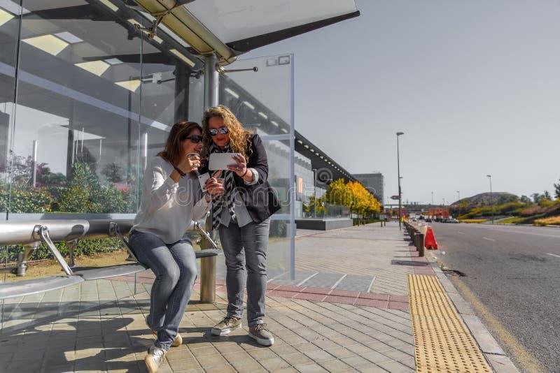 Deux amis féminins passent en revue un comprimé, alors qu'ils prennent un café et attendent à un arrêt d'autobus photographie stock libre de droits