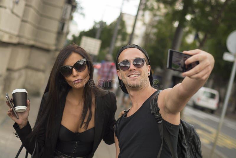 Deux amis gais prenant des photos de lui-même au téléphone intelligent photographie stock libre de droits