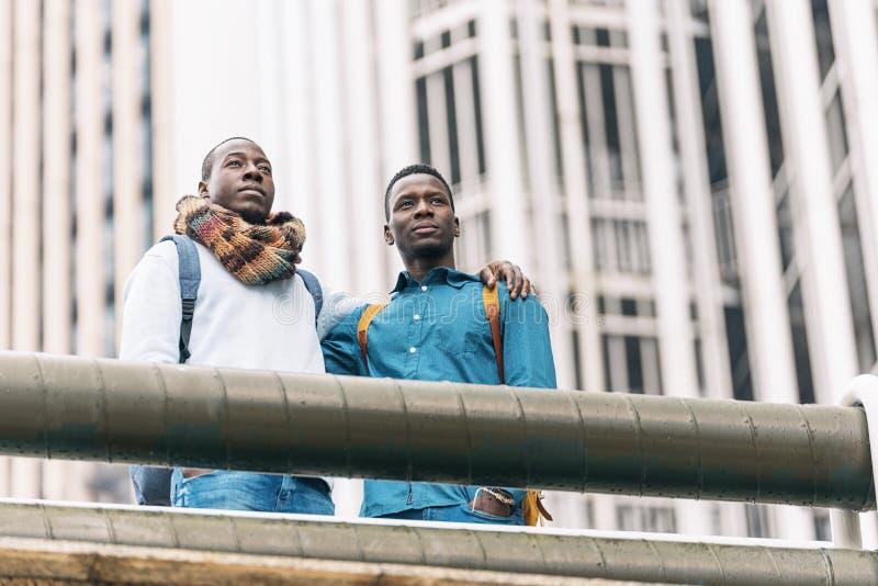 Deux amis grêlent des autres personnes dans la rue photo libre de droits