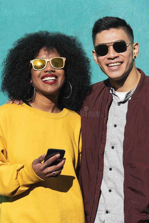 Deux amis heureux employant le mobile dans la rue image libre de droits