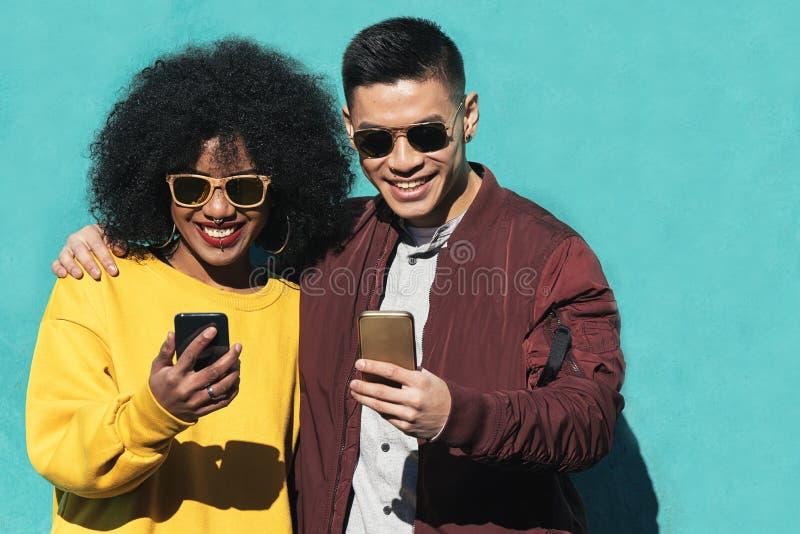 Deux amis heureux employant le mobile dans la rue Concept d'amitié photographie stock libre de droits