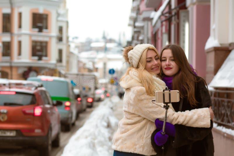 Deux amis heureux prenant un selfie à la rue utilisant le phone futé images stock