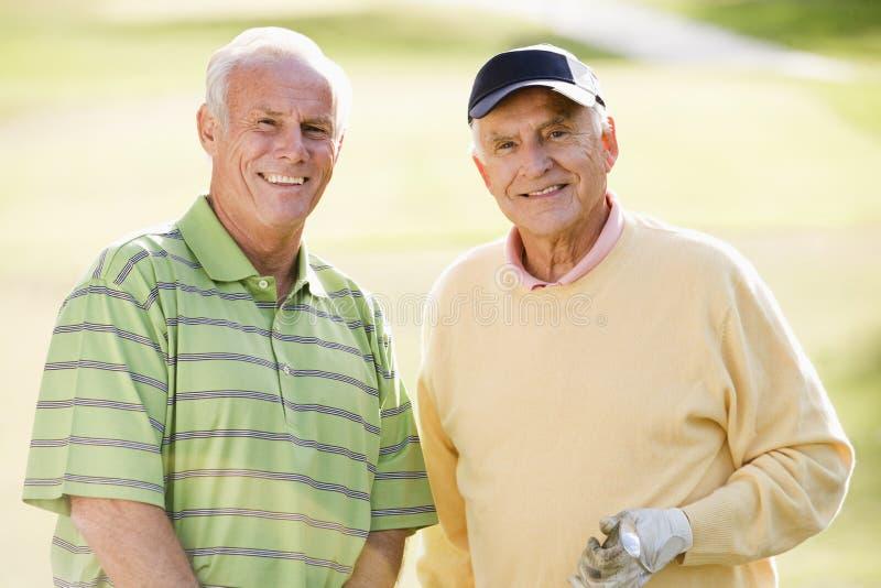 Deux amis mâles appréciant le jeu du golf image stock