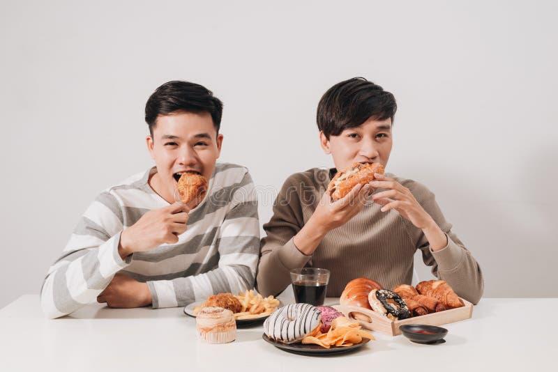 Deux amis mangeant des hamburgers pommes frites, ayant l'amusement et le sourire photos libres de droits