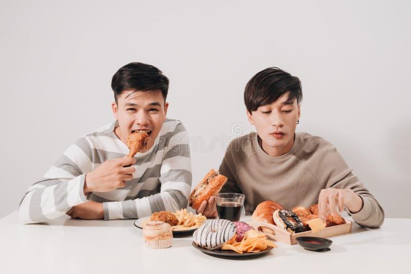 Deux amis mangeant des hamburgers pommes frites, ayant l'amusement et le sourire photo stock