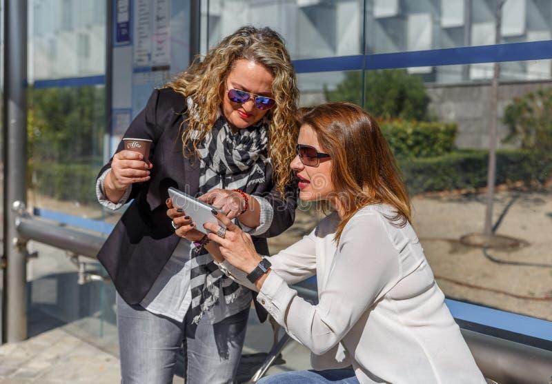 Deux amis parlent, vérifient un périphérique mobile et prendre un café tout en attendant à un arrêt d'autobus, un jour d'automne photo stock