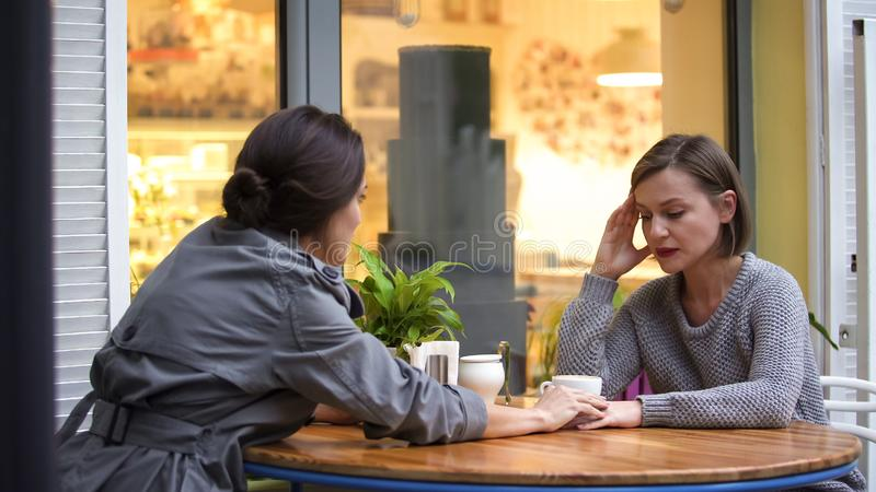 Deux amis s'asseyant en café discutant des problèmes de famille, dame soulageant la soeur images libres de droits