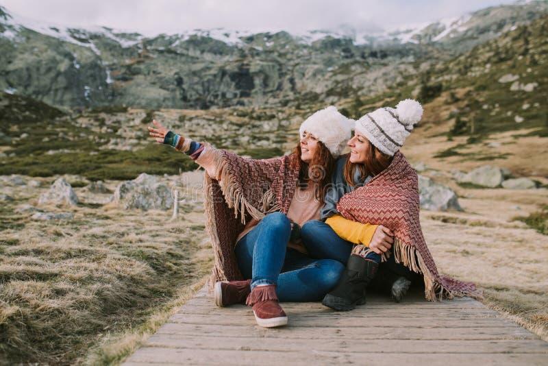 Deux amis s'asseyent dans le pré se sont enveloppés dans une couverture pendant qu'ils regardent et indiquent un endroit images libres de droits
