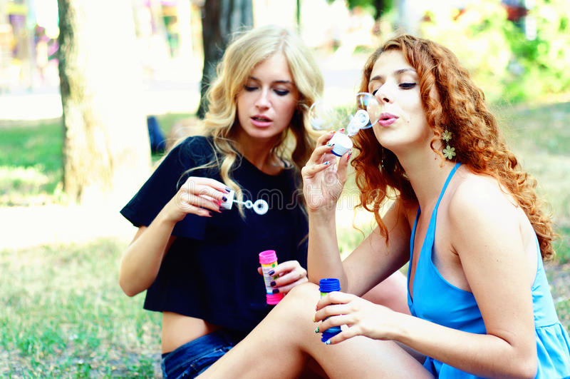 Deux amis soufflant des bulles de savon images stock