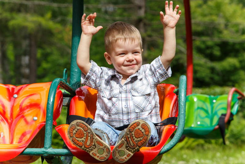 Deux-année-vieille équitation courageuse de garçon sur le carrousel image libre de droits